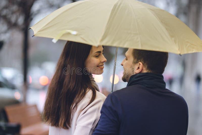 Los pares hermosos, el individuo y su novia vestidos en ropa casual se colocan debajo del paraguas y miran uno a encendido imagenes de archivo