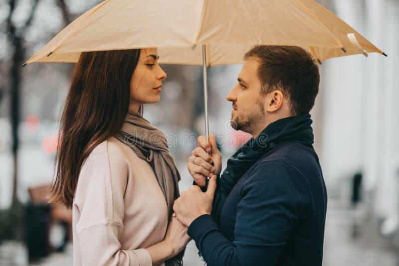 Los pares hermosos, el individuo y su novia vestidos en ropa casual se colocan debajo del paraguas y miran uno a encendido foto de archivo