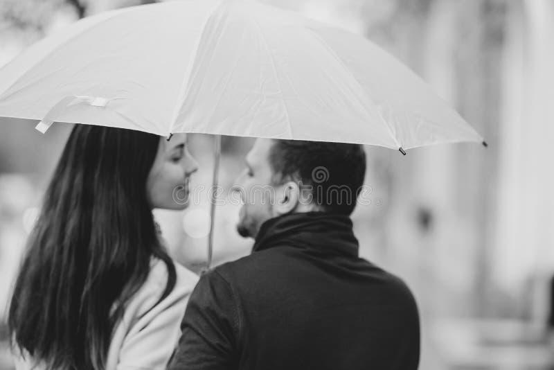Los pares hermosos, el individuo y su novia vestidos en ropa casual se colocan debajo del paraguas y miran uno a encendido imagen de archivo