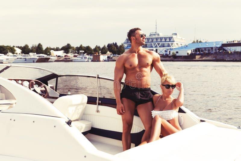 Los pares hermosos elegantes en el barco en una nadada llevan imagen de archivo libre de regalías