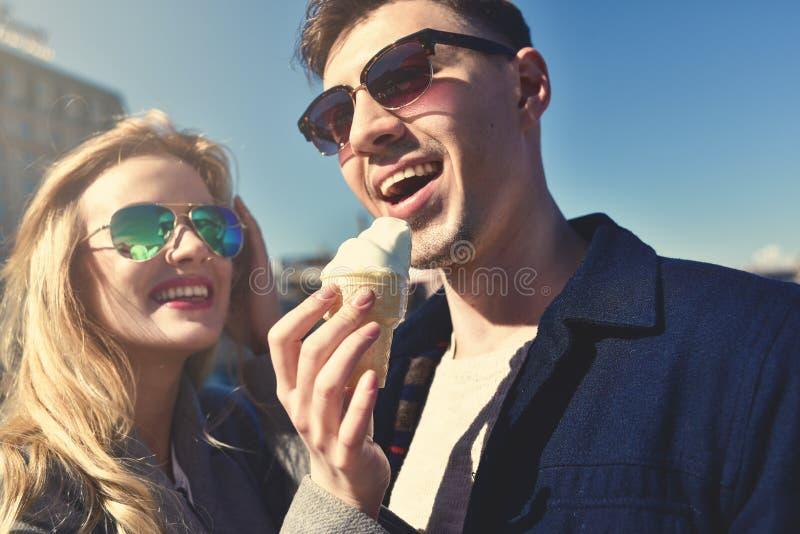 Los pares hermosos permanecen en el terraplén de la ciudad y la consumición del helado imagen de archivo libre de regalías