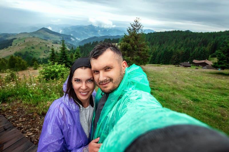 Los pares hermosos, turistas, hacen el selfie, foto contra la perspectiva de las montañas cárpatas hermosas Concepto del viaje, fotos de archivo libres de regalías