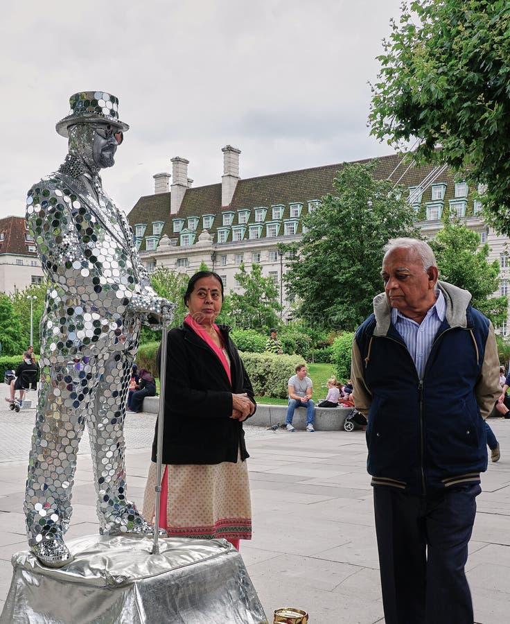 Los pares indios comprueban hacia fuera al ejecutante duplicado inm?vil, de plata de la calle en Londres, Inglaterra foto de archivo