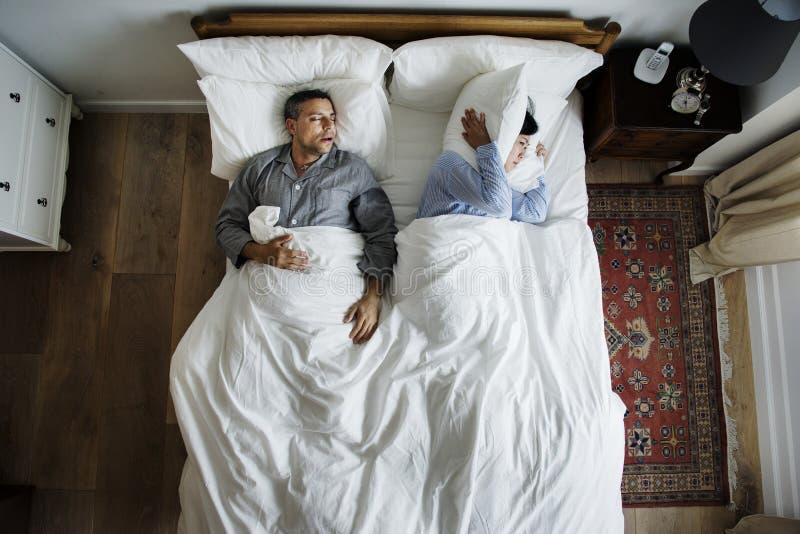 Los pares interraciales en la cama sirven a la mujer que ronca y de interrupción foto de archivo libre de regalías