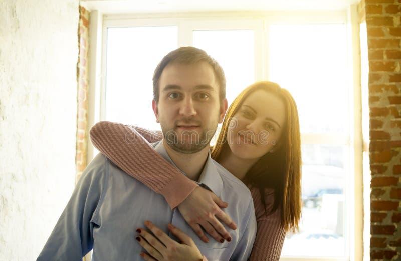 Los pares jovenes abrazan la opinión panorámica grande de la ventana del apartamento moderno, el hombre de la raza de la mezcla y foto de archivo libre de regalías