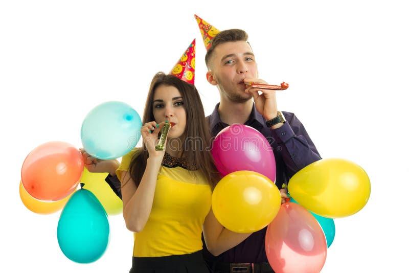 Los pares jovenes alegres con los globos coloreados celebran cumpleaños fotos de archivo
