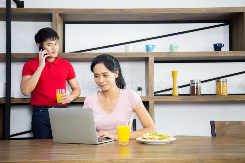 Los pares jovenes asiáticos, mujer están mirando negocio en ordenador portátil y detrás tienen un hombre que habla el teléfono mó imagen de archivo