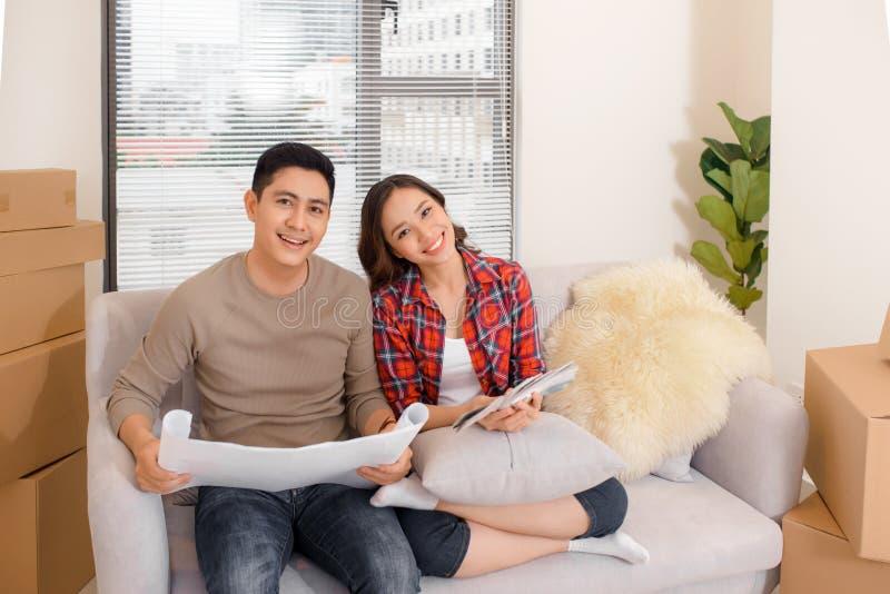 Los pares jovenes asiáticos planean el interior de la nueva casa Leyeron bluepri imagen de archivo libre de regalías