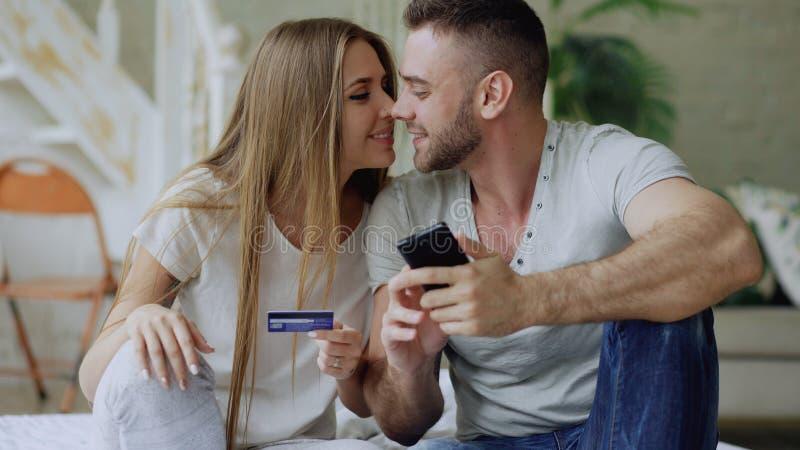 Los pares jovenes atractivos con compras de la tarjeta del smartphone y de crédito en Internet se sientan en cama en casa fotografía de archivo libre de regalías