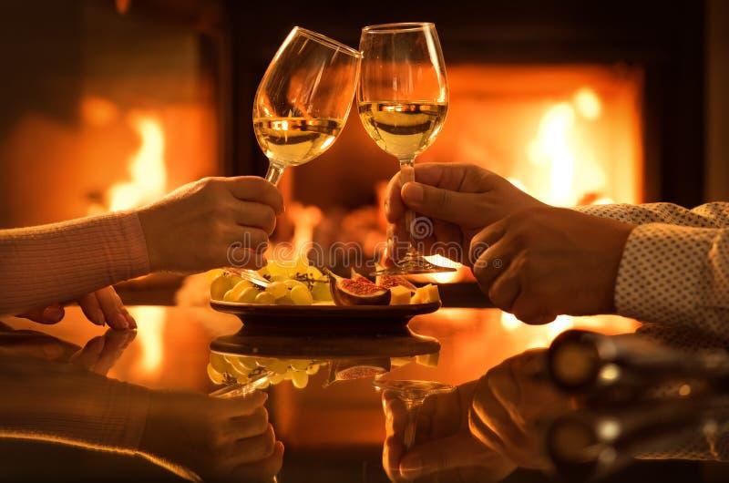 Los pares jovenes cenan romántico con el vino sobre fondo de la chimenea fotografía de archivo