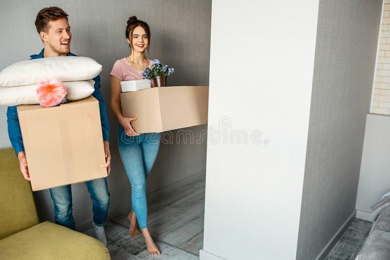 Los pares jovenes de la familia compraron o alquilaron su primer pequeño apartamento La gente alegre feliz entra en el sitio con  foto de archivo