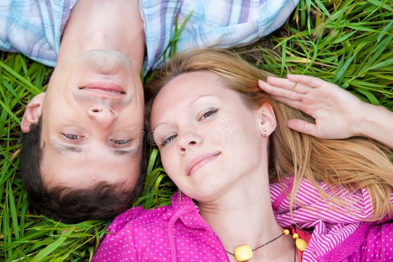 Los pares jovenes del amor ponen en la hierba verde al aire libre. fotografía de archivo