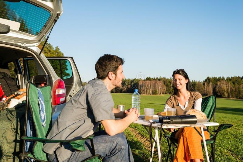 Los pares jovenes del coche que acampa gozan del campo de la comida campestre fotografía de archivo