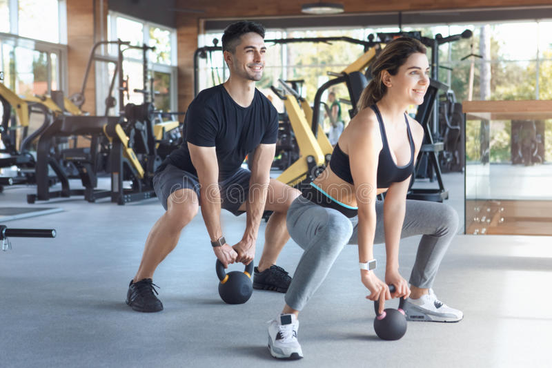 Los pares jovenes ejercitan juntos en forma de vida sana del gimnasio imagen de archivo libre de regalías