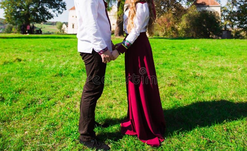 Los pares jovenes en el amor que camina en el otoño parquean sostener lo de las manos foto de archivo