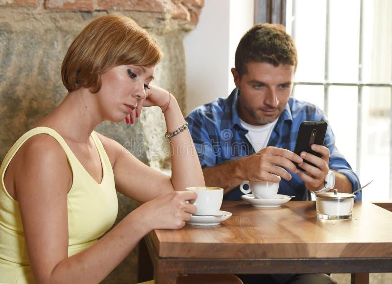 Los pares jovenes en la cafetería con el adicto a Internet y al teléfono móvil sirven la negligencia de la mujer frustrada fotografía de archivo libre de regalías