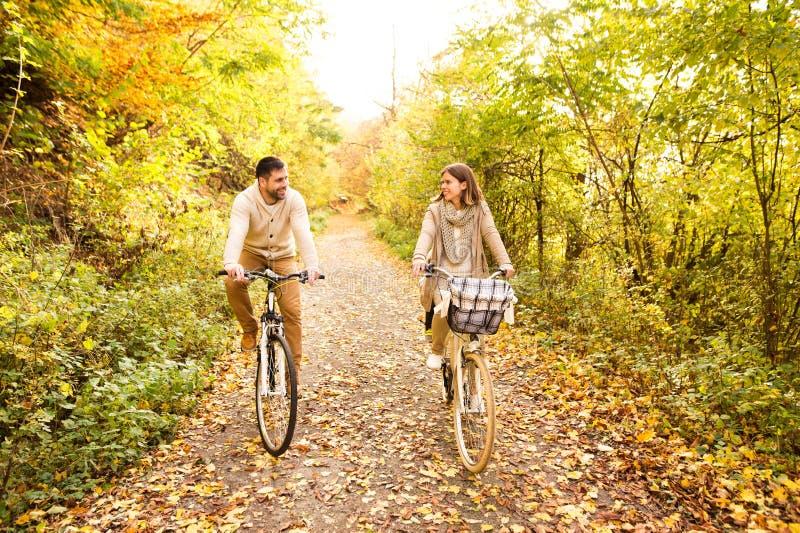 Los pares jovenes en la ropa caliente que completa un ciclo en otoño parquean foto de archivo libre de regalías