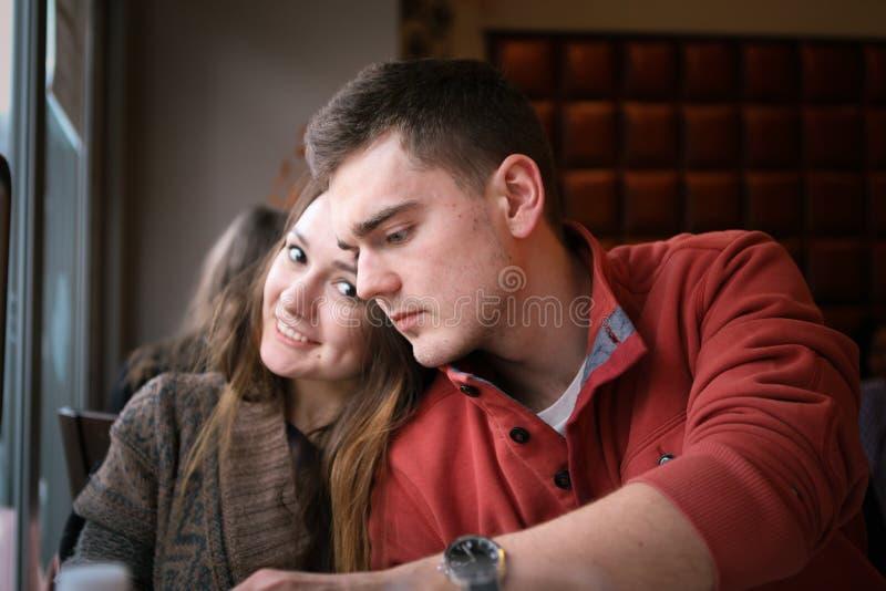 Los pares jovenes en un restaurante que se sienta en una tabla por la ventana y hacen una orden Dos personas fotografía de archivo libre de regalías