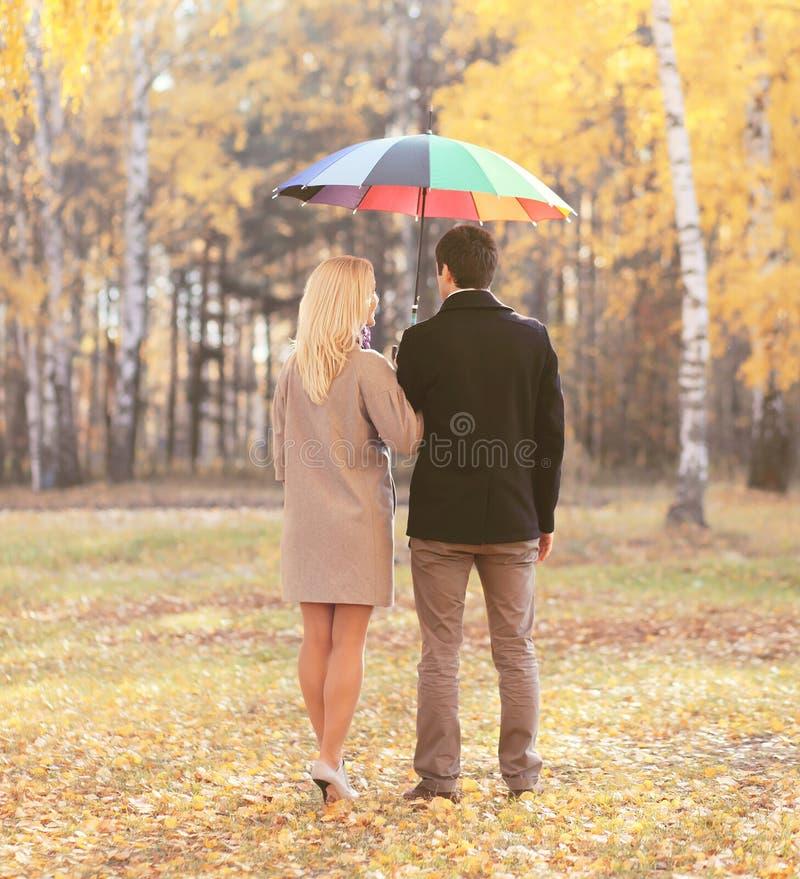 Los pares jovenes felices así como el paraguas en otoño parquean foto de archivo libre de regalías