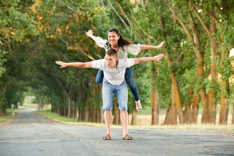 Los pares jovenes felices caminan en la carretera nacional al aire libre, concepto romántico de la gente, estación de verano fotos de archivo