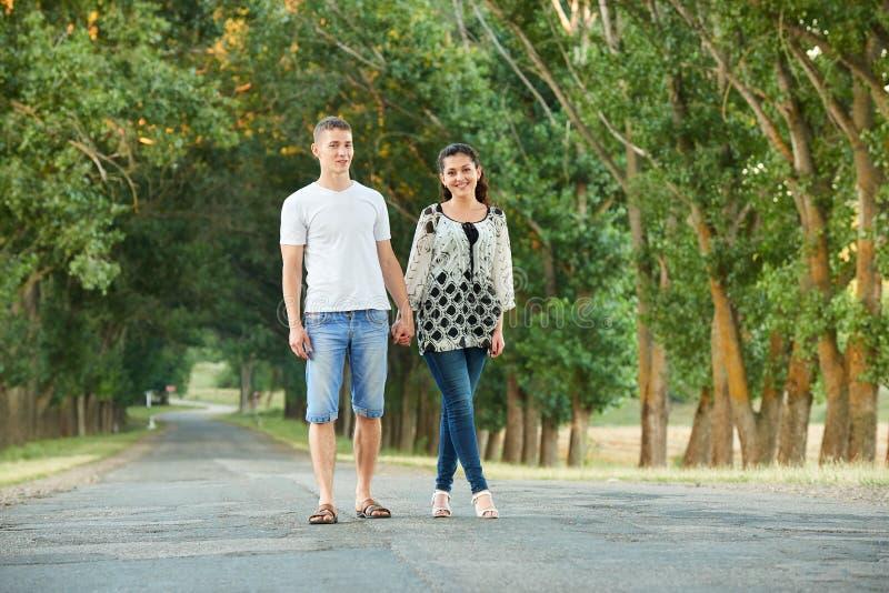 Los pares jovenes felices caminan en la carretera nacional al aire libre, concepto romántico de la gente, estación de verano fotografía de archivo