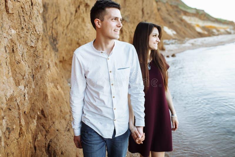 Los pares jovenes, felices, cariñosos, cerca de la pared de la arena, en el mar, llevando a cabo las manos van mirar uno a, la pu fotos de archivo libres de regalías