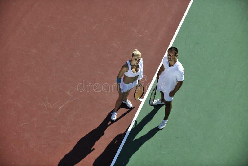Los pares jovenes felices juegan al juego del tenis al aire libre imagen de archivo libre de regalías