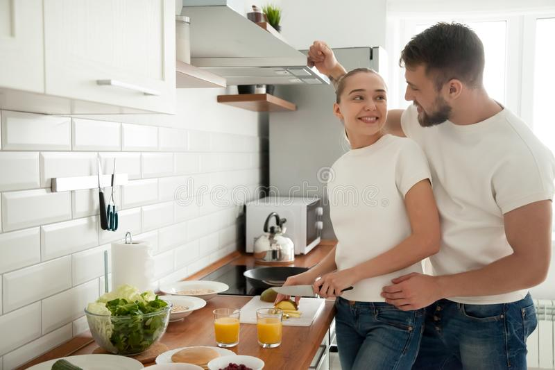 Los pares jovenes felices preparan el desayuno en cocina juntos imagen de archivo libre de regalías