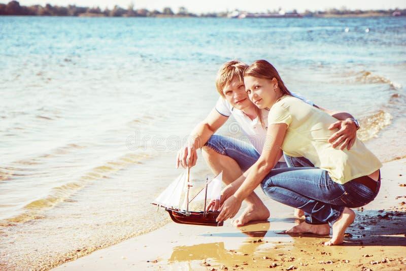 Los pares jovenes felices que disfrutan de comida campestre en la playa y tienen buen ti imagen de archivo