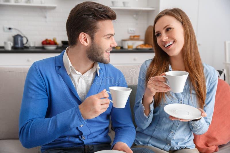 Los pares jovenes junto en casa weekend hablar de consumición del café foto de archivo