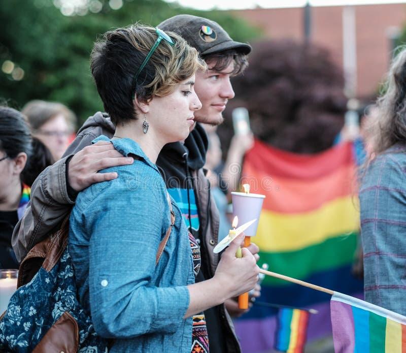 Los pares jovenes llevan a cabo velas en la vigilia de Corvallis para las muertes del tiroteo de Orlando imágenes de archivo libres de regalías