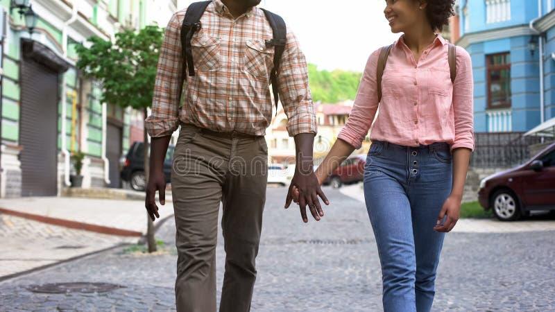 Los pares jovenes que caminan llevando a cabo las manos, recienes casados vacation, ocio activo, turismo foto de archivo