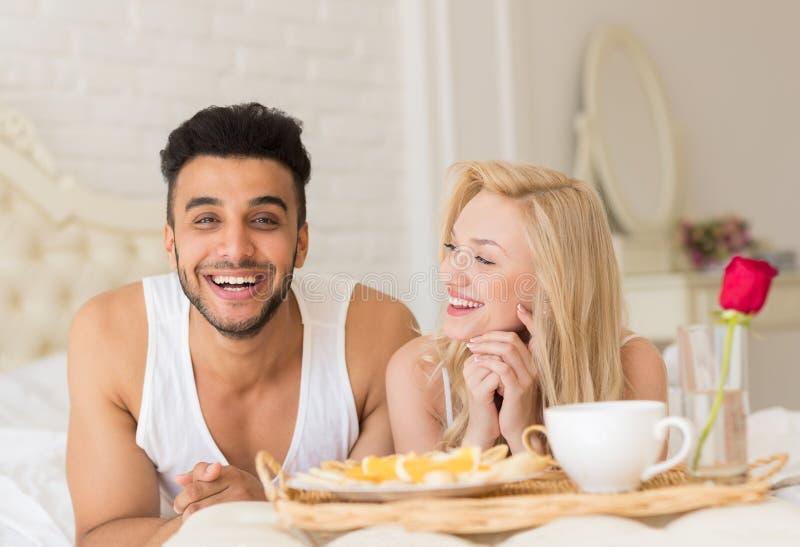 Los pares jovenes que mienten en cama comen mañana del desayuno con Rose Flower roja, el hombre de la sonrisa feliz y la mujer hi fotos de archivo