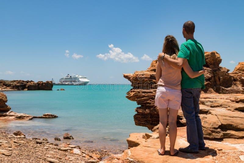 Los pares jovenes que miraban el barco de cruceros moderno ataron hasta el embarcadero fotos de archivo libres de regalías