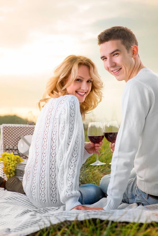 Los pares jovenes que se sientan en una comida campestre con la cesta y la bebida blancas ganan fotos de archivo libres de regalías