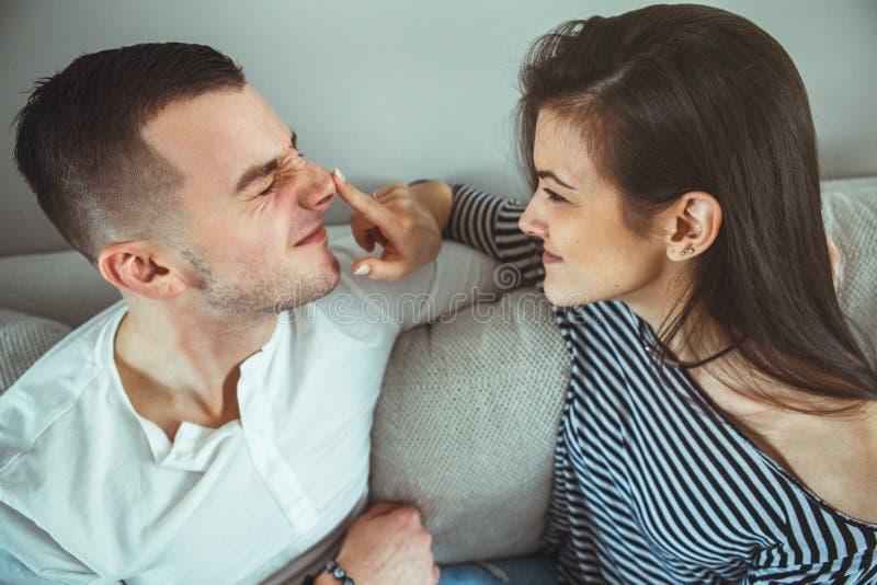 los pares jovenes románticos de risa sonrientes sirven a la mujer en el amor que se divierte, dentro en casa sentándose en el sof foto de archivo