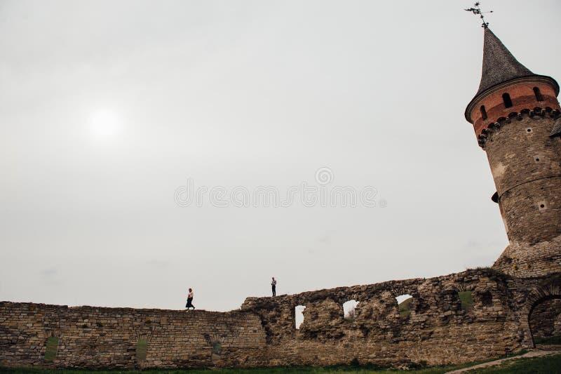 Los pares jovenes se divierten cerca del castillo medieval foto de archivo