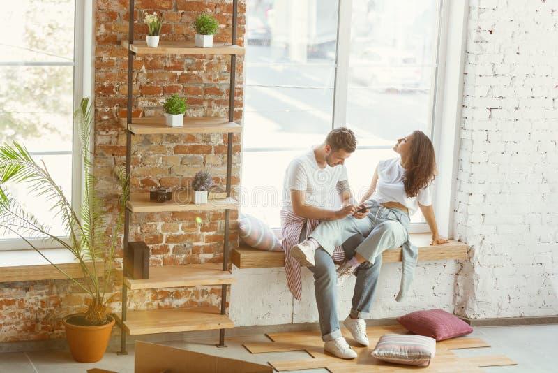 Los pares jovenes se movieron a una nueva casa o a un apartamento foto de archivo libre de regalías