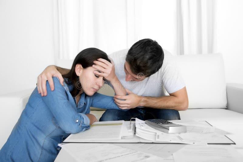 Los pares jovenes se preocuparon a casa en el marido de la tensión que confortaba a la esposa en problemas financieros foto de archivo libre de regalías