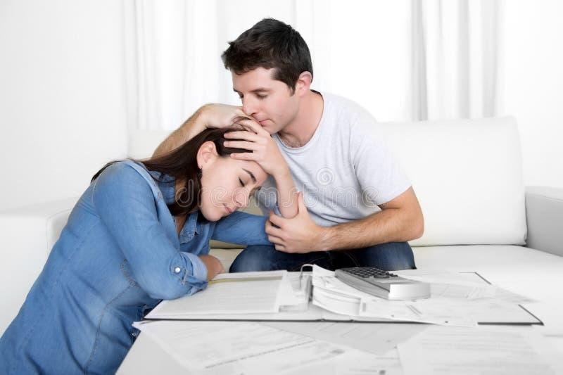 Los pares jovenes se preocuparon a casa en el marido de la tensión que confortaba a la esposa en problemas financieros fotografía de archivo