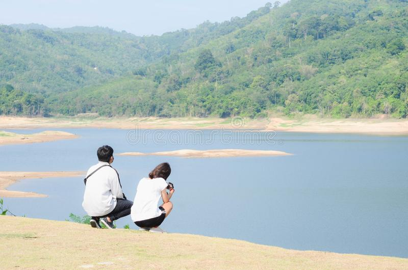 Los pares jovenes se relajan al lado de la presa despu?s de activar imagen de archivo libre de regalías