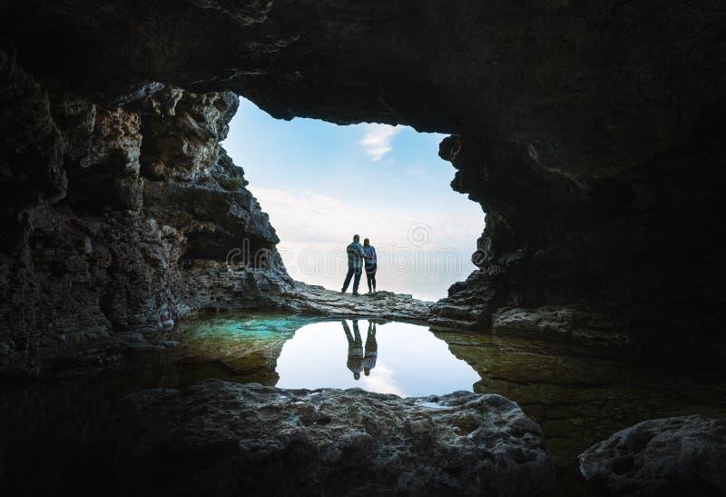 Los pares jovenes se unen en la boca de una gruta fotos de archivo libres de regalías