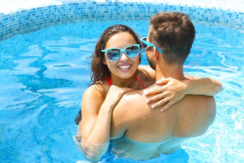 Los pares jovenes son relajantes en piscina fotografía de archivo