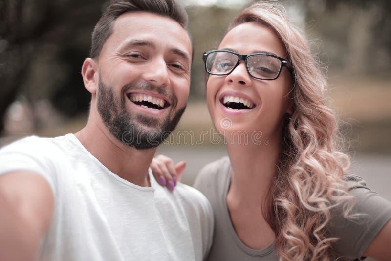 Los pares jovenes sonrientes en el fondo de la ciudad parquean imagen de archivo