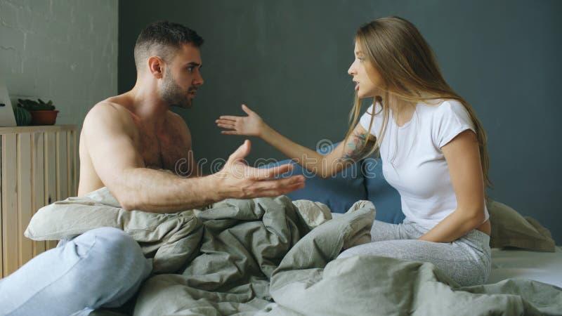 Los pares jovenes trastornados en sentarse en cama trastornan y se discuten foto de archivo libre de regalías