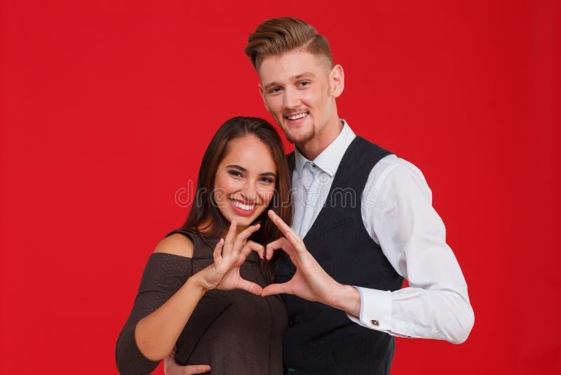 Los pares jovenes y hermosos en amor hacen un corazón en un fondo rojo El concepto de día del ` s de la tarjeta del día de San Va imagenes de archivo
