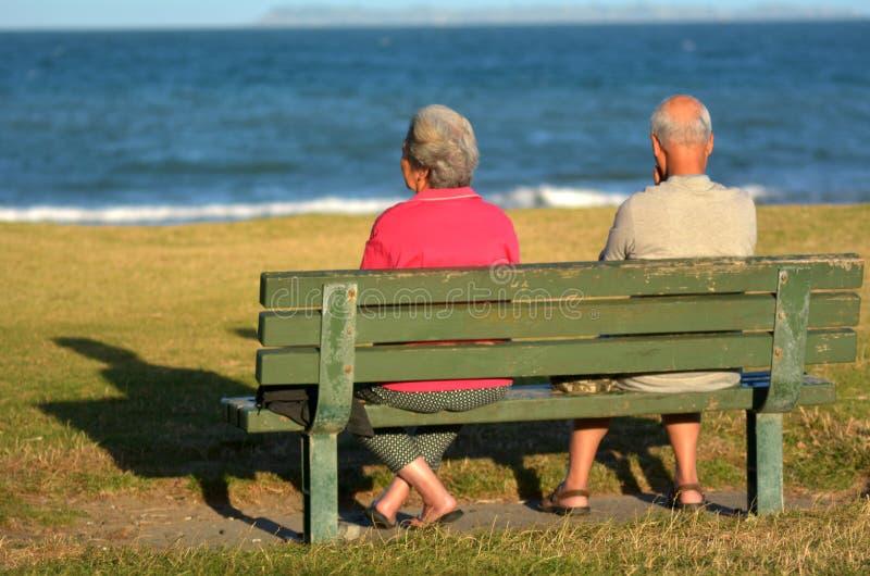 Los pares jubilados se sientan en un banco foto de archivo libre de regalías