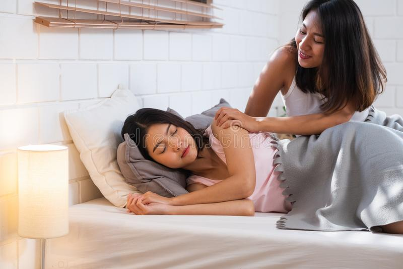 Los pares lesbianos felices despiertan en cama en dormitorio por mañana y se abrazan en casa Concepto de la forma de vida de LGBT imágenes de archivo libres de regalías