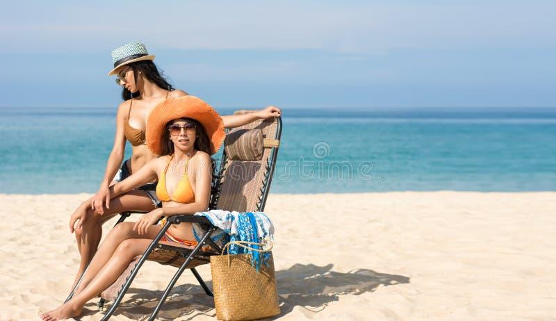 Los pares lesbianos se están sentando en la playa mientras que relajan vacaciones o fin de semana imagen de archivo