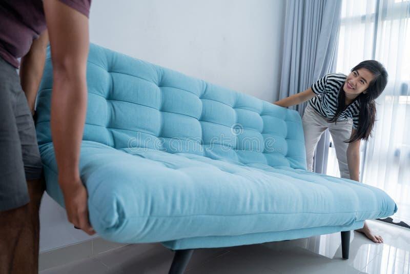Los pares levantan un sofá y un movimiento al nuevo hogar imágenes de archivo libres de regalías